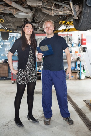 Portrait of young mechanic standing with female customer in auto repair shop photo