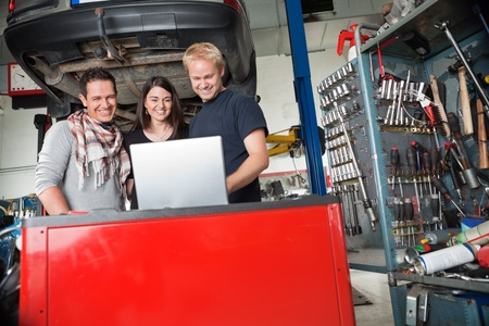 Young smiling couple standing with mechanic using laptop in auto repair shop Stock Photo - 10337029