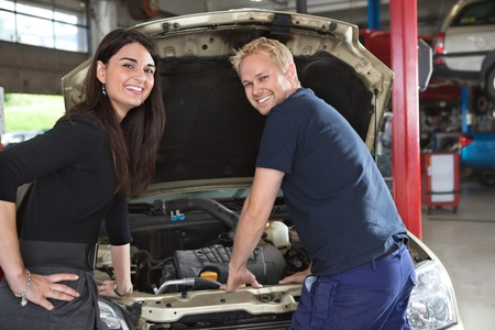 two car garage: Portrait of happy female customer and mechanic in garage Stock Photo