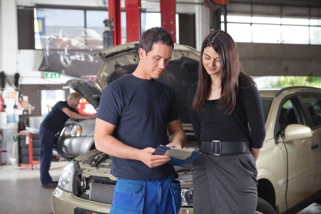 automobile workshop: Mechanic showing the cost of service to female client while man working in background