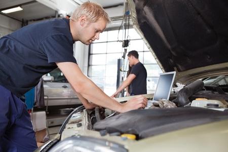 garage automobile: Mécanicien utilisant un ordinateur portable tout en travaillant sur la voiture avec des gens en arrière-plan