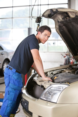 livelihood: Portrait of a mechanic man leaning on car in garage Stock Photo