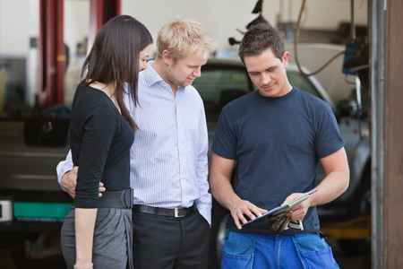car workshop: Mature couple standing with mechanic outside the garage