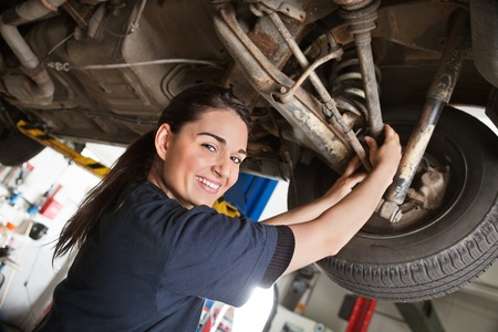 Portrait of smiling young female mechanic inspecting a CV joing on a car in auto repair shop photo