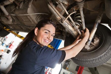 mecanico: Taller de reparaciones de retrato de sonriente joven mec�nico femenina inspeccionando un CV impartiendo en un coche en auto