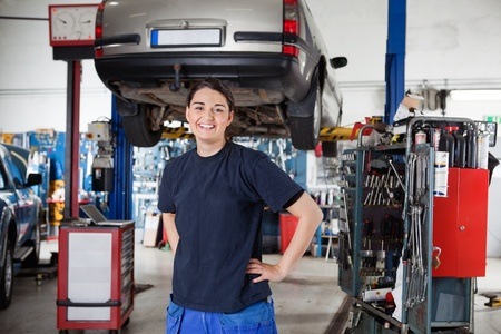car in garage: Portrait of smiling young female mechanic with hands on hips in auto repair shop Stock Photo