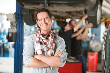 gl�cklicher kunde: Portr�t eines m�nnlichen gl�cklich Kunden in ein Auto Reparaturwerkstatt mit Mechanik im Hintergrund