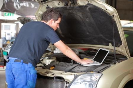 駐車場に車を修復中にラップトップを使用してメカニック