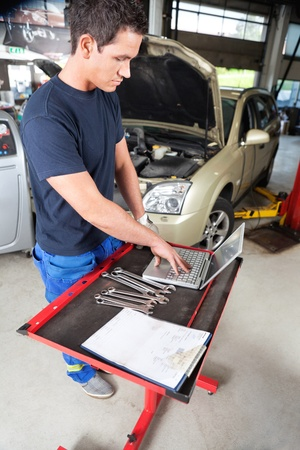 automobile workshop: Serious looking mechanic working on a laptop in garage Stock Photo
