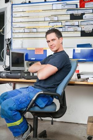 Mécanicien avec les bras croisés assis sur une chaise et souriant