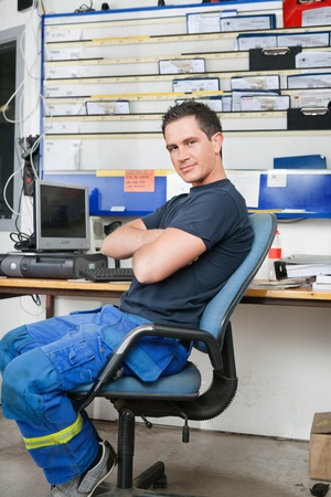 auto repair shop: Mechanic with arms crossed sitting on a chair and smiling