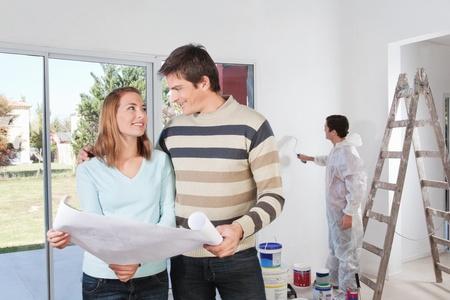 pintor de casas: Joven pareja mirando mutuamente con el pintor en segundo plano Foto de archivo