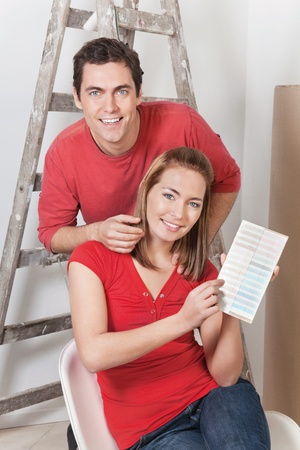 Young happy couple pointing at color card photo