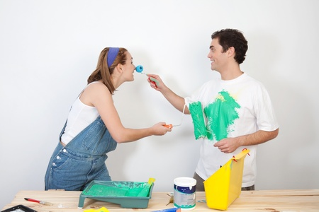 mischievous: Smiling man painting his wifes nose with paint Stock Photo