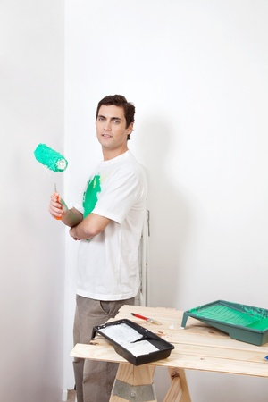 Portrait of man holding paint roller at home photo