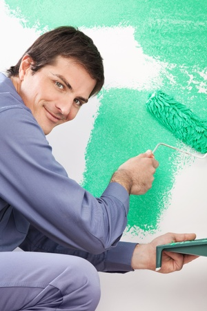 Portrait of smiling handsome man painting his house with roller photo