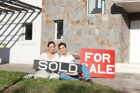 Couple holding sold sign and keys against their new house photo