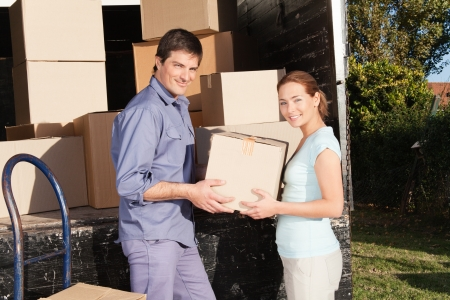 Smiling couple moving luggage at their new house photo