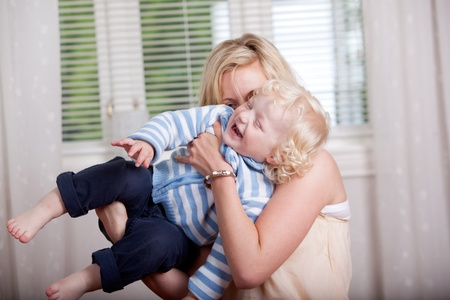 Portrait of a mother and son laughing and joking together photo