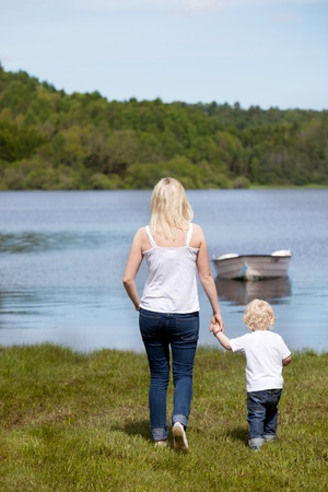 A mother walking with her son hear a lake with a small boat photo