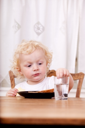 A young child sitting a a table reaching for glass of water photo