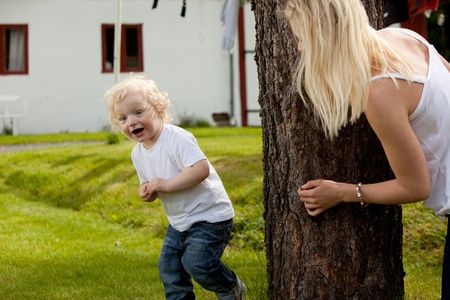 hide and seek: An extremely excited young boy looking for his mother playing hide and seek