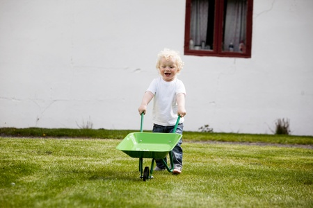 barrow: A young child pushing a wheelbarrow outdoors in a rural farm setting