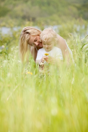 A happy cheeful mother and son in green picturesque meadow photo