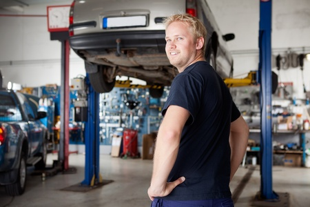 auto lift: A happy smiling mechanic in an autio repair shop, looking at the camera
