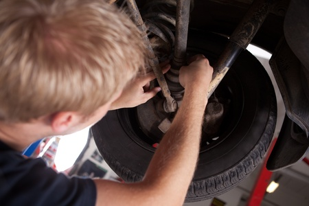 A blond male mechanic inspecting a CV joing on a car photo