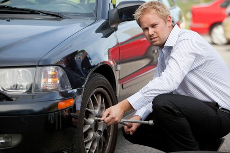 inconvenience: An unhappy business man changing a tire on the road