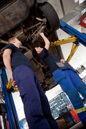 service lift: A Man and Woman mechanic looking at a car, assessing a repair