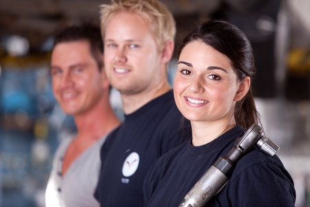 shop skill: Portrait of a team of mechanics with a woman in the forground Stock Photo