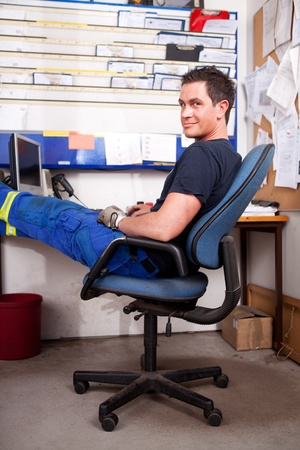 slack: A relaxed auto mechanic leaning back in a chair in an office Stock Photo