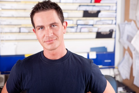 auto garage: Portrait of a young man mechanic in office
