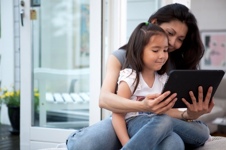 Mother and Daughter having fun on a digital tablet in a home interior photo