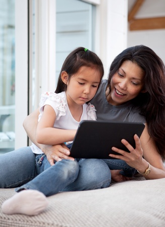 A cute happy mother and daughter using a digital tablet at home in the living room photo