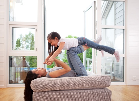 Playful mother giving daughter an airplane ride with arms and feet Stock Photo - 10393417