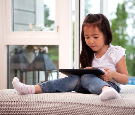 Portrait of a young child in a home interior engrossed in a game on a digital tablet photo