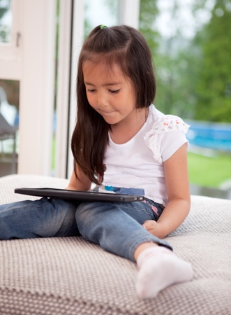 Young girl child looking at a digital tablet sitting on a couch cushion photo