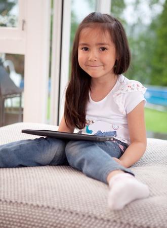 asian home: Ritratto di un bambino cute giovane a casa utilizzando una tavoletta digitale, guardando la telecamera