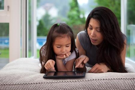mamans: M�re et fille pose sur le divan en jouant avec une tablette num�rique Banque d'images