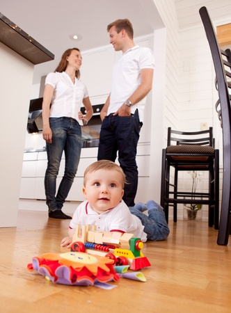 A young child boy playing on the kitchen floor with happy parents talking in the background Stock Photo - 10393423