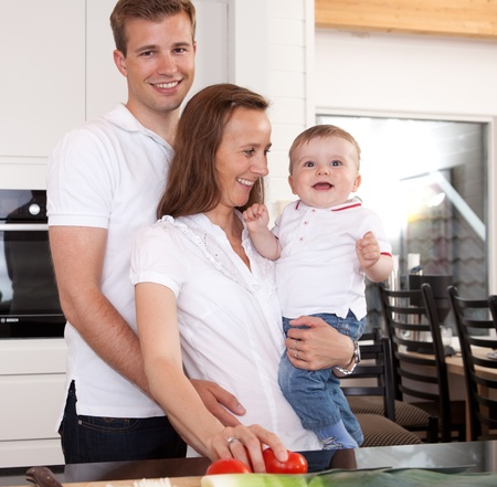 Happy family preparing meal with father giving the mother a hug Stock Photo - 10393407