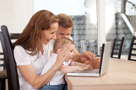 webcam: A happy family talking through the computer with video chat Stock Photo