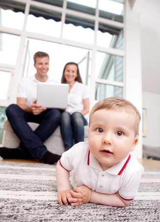 A happy curious young baby boy with parents in the background using computer photo