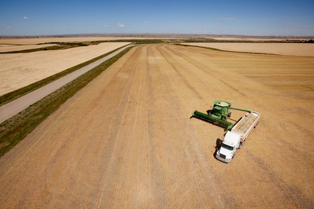 Aerial shot of a combine emptier a hopper into a semi truck on the prairie photo