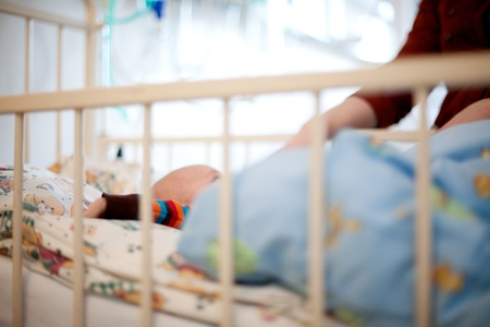 pediatrics: Abstract of a young baby in a hospital bed with mother beside