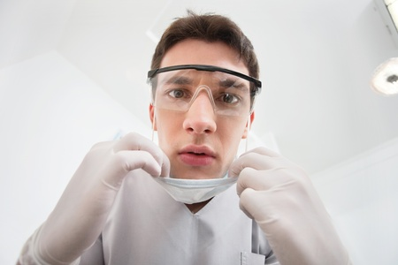 Close-up of young male dentist wearing mask photo