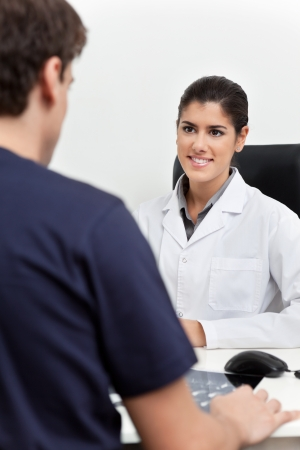 comunicacion oral: Joven doctora hablando al paciente en su Oficina Foto de archivo